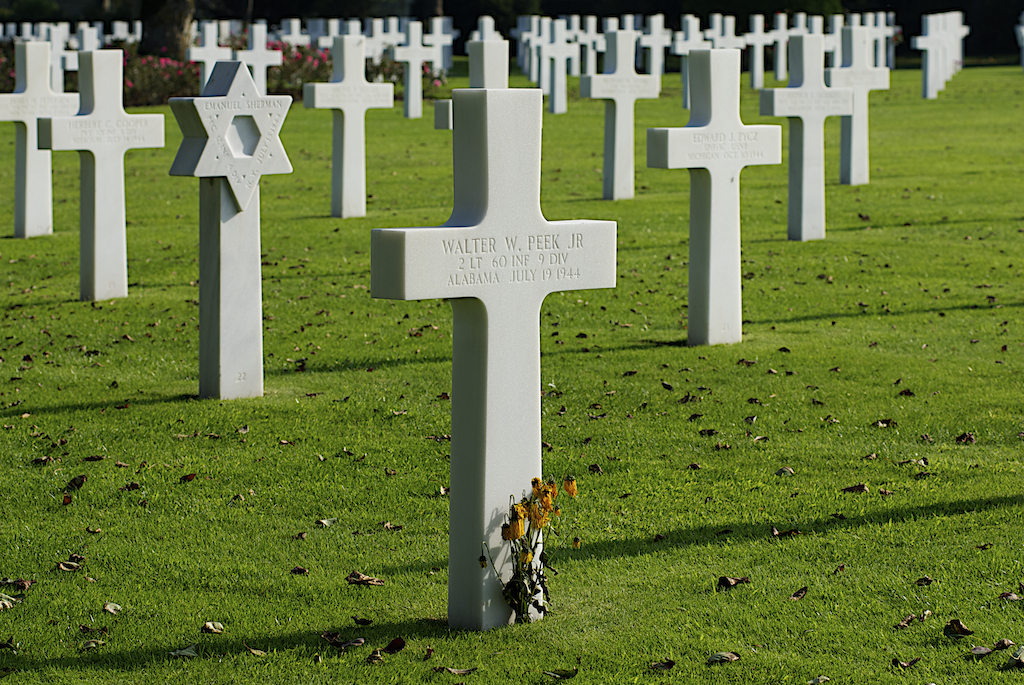 A Jewish soldier's grave with six pointed Jewish star amongst hundreds of crosses, dead flowers sit at base of closest cross