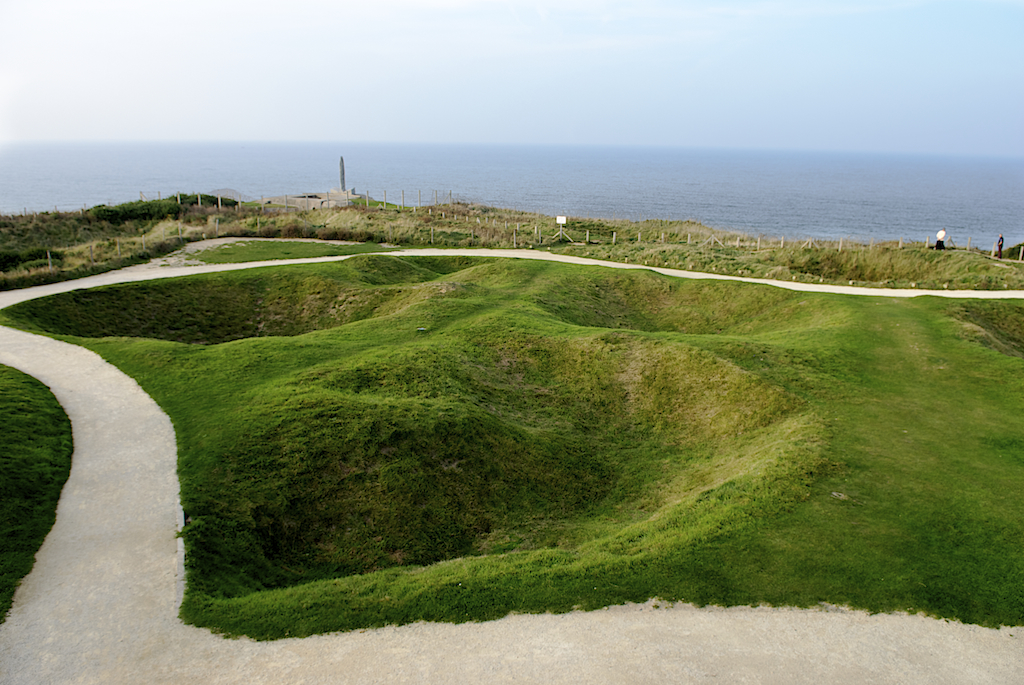 bomb craters at Omaha beach look like giant, deep golf sand traps without the sand