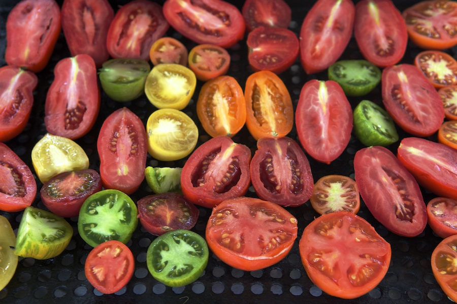 tomatoes, halved and pepper on glass table ready to grill