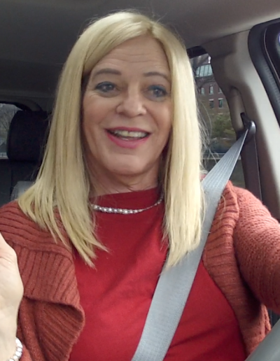 Jamie driving, in a long blonde wig