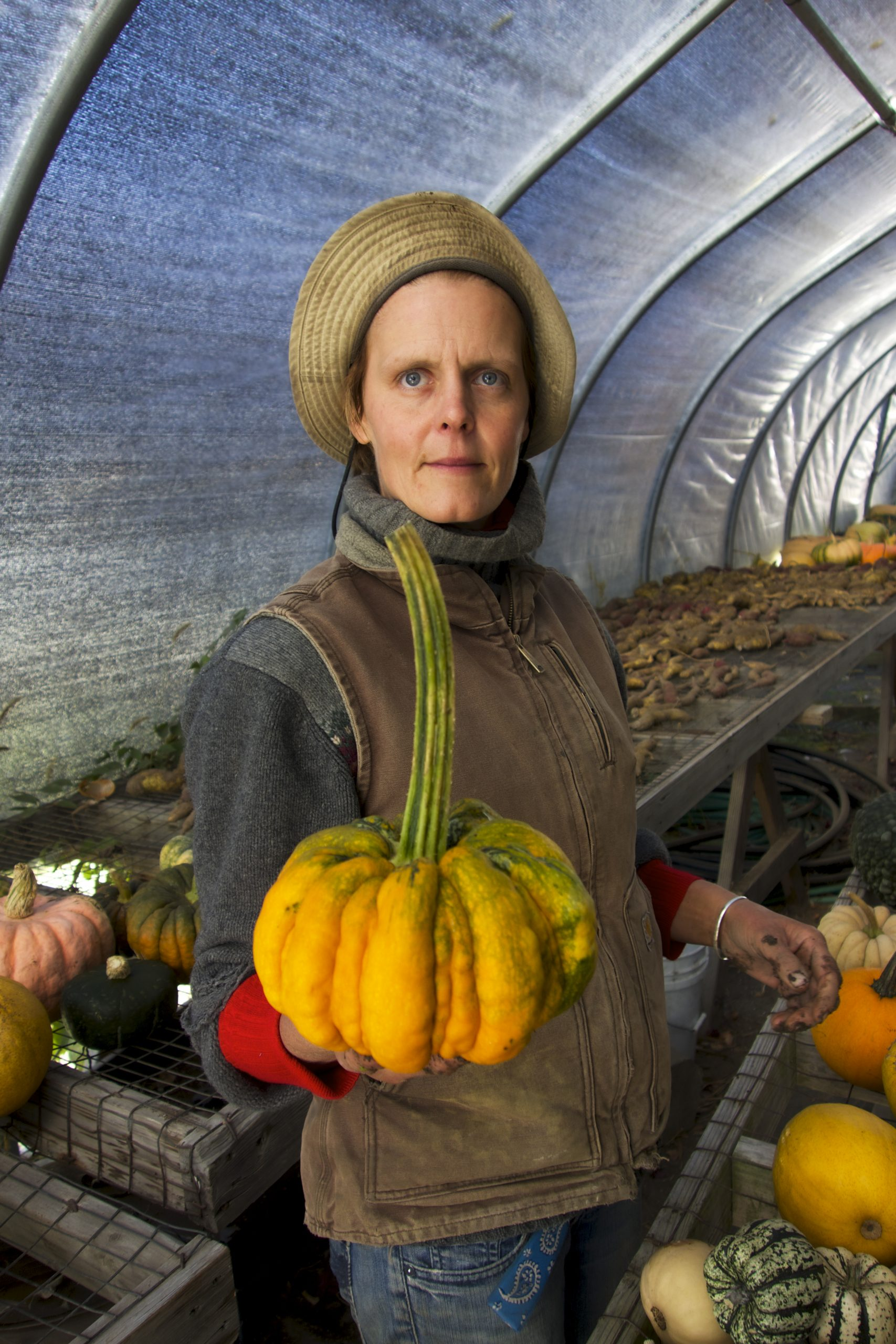 Patty Gentry in greenhouse holding up pumpkin with very long stem