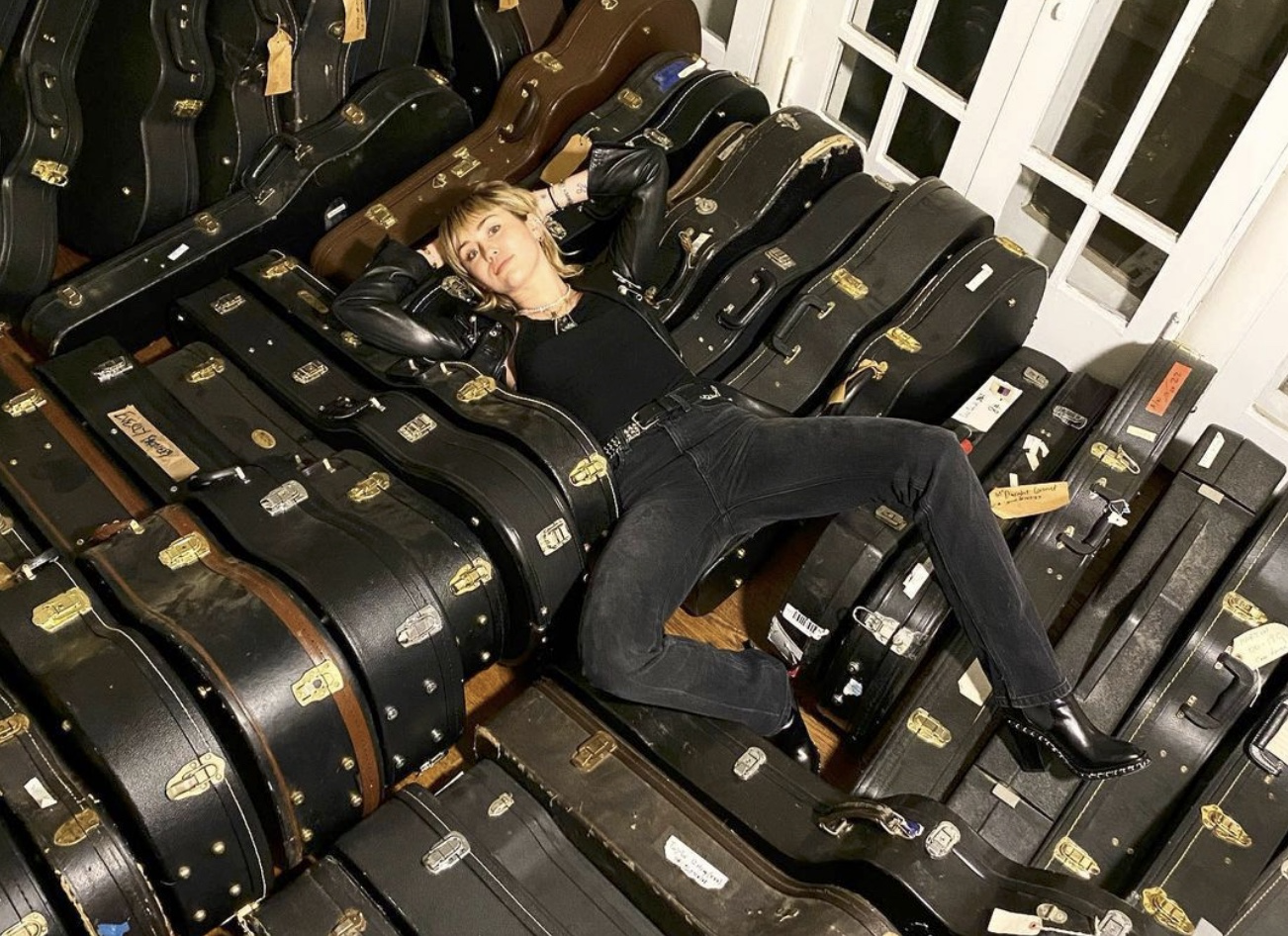 Miley Cyrus lying on dozens of guitar cases